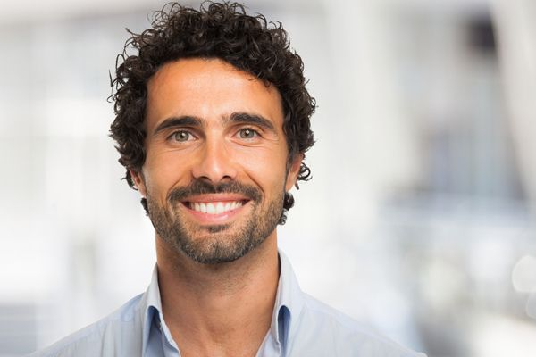 curly haired man smiling