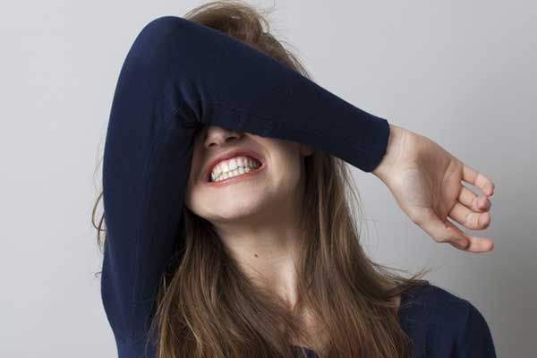 girl covering her eyes with elbow and arm