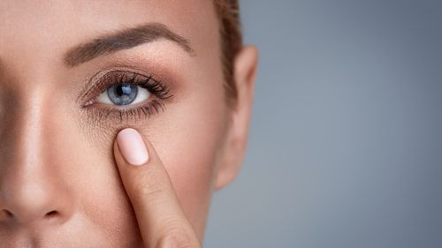 woman with her finger near her eye