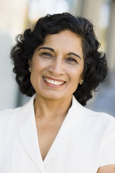 middle-aged woman with curly hair smiling