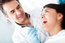 A dentist examines one of his patients