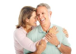 Embracing older couple with healthy teeth