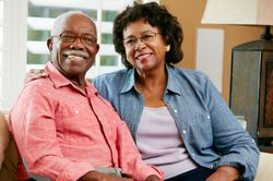 Seated in an office lobby, a senior couple smiles at the camera