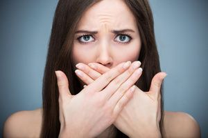 woman covers her mouth